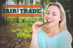 Составное изображение довольно белокурого наслаждаться и еды бара шоколада Стоковое фото RF