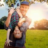 Составное изображение отца держа его сына вверх ногами Стоковое Фото