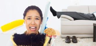 Составное изображение очень усиленной женщины с инструментами чистки Стоковое фото RF