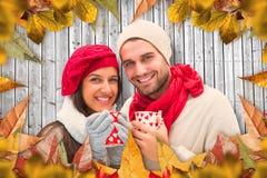 Составное изображение пар зимы держа кружки Стоковые Изображения RF