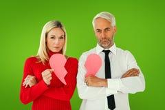 Составное изображение пар не говоря держащ 2 половины разбитого сердца Стоковые Изображения RF