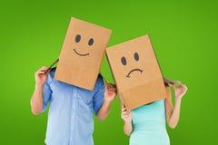 Составное изображение пар нося унылые коробки стороны на их головах Стоковые Изображения RF