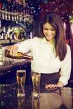 Составное изображение пива женского бармена лить в стекла стоковое изображение