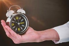 Составное изображение подрезанной руки мужского исполнительного держа будильника Стоковая Фотография RF