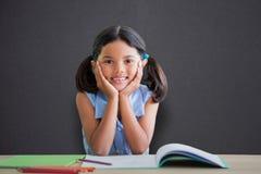 Составное изображение портрета девушки делая домашнюю работу на столе Стоковое фото RF