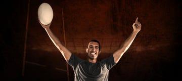 Составное изображение портрета игрока рэгби в голубом jersey держа шарик с оружиями поднятый Стоковые Фото