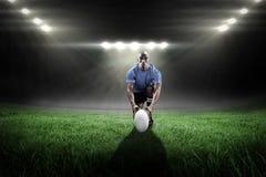 Составное изображение портрета игрока рэгби держа шарик пока встающ на колени Стоковое фото RF