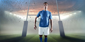 Составное изображение портрета игрока рэгби смотря отсутствующий пока держащ шарик в сторону Стоковое Изображение RF