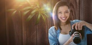 Составное изображение портрета усмехаясь женского фотографа держа цифровой фотокамера Стоковые Изображения