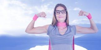 Составное изображение портрета усмехаясь женщины в костюме супергероя пока изгибающ muscles Стоковые Фотографии RF