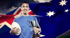 Составное изображение портрета усмехаясь игрока рэгби держа трофей и шарик Стоковая Фотография