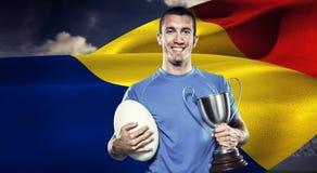 Составное изображение портрета усмехаясь игрока рэгби держа трофей и шарик Стоковое Фото