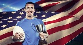 Составное изображение портрета усмехаясь игрока рэгби держа трофей и шарик Стоковое фото RF