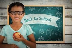 Составное изображение портрета усмехаясь eyeglasses девушки нося держа яблоко Стоковое Фото