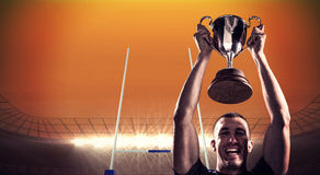 Составное изображение портрета успешного игрока рэгби держа трофей Стоковое Изображение