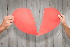 Составное изображение подрезанных пар вручает держать красную треснутую форму сердца стоковая фотография rf