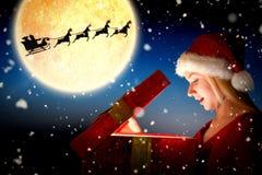 Составное изображение праздничной блондинкы раскрывая подарок стоковое фото
