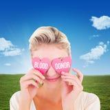 Составное изображение привлекательных молодых белокурых держа сердец над глазами Стоковая Фотография
