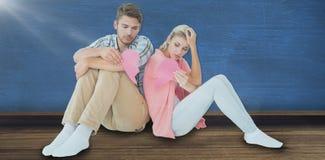 Составное изображение привлекательных молодых пар сидя держащ 2 половины разбитого сердца Стоковые Фотографии RF