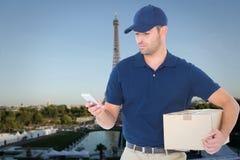 Составное изображение работника доставляющего покупки на дом используя мобильный телефон пока держащ пакет Стоковое фото RF