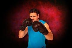 Составное изображение решительно мужского боксера сфокусировало на его тренировке Стоковые Изображения RF