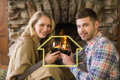 Составное изображение романтичных пар провозглашать рюмки перед освещенным камином Стоковое Изображение RF