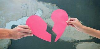 Составное изображение рук держа 2 половины разбитого сердца Стоковая Фотография RF