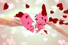Составное изображение рук держа 2 половины разбитого сердца Стоковое Изображение