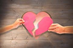 Составное изображение рук держа 2 половины разбитого сердца Стоковое фото RF
