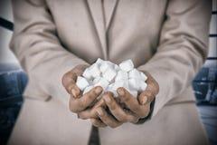 Составное изображение рук женщины приданных форму чашки с кубами сахара Стоковое фото RF