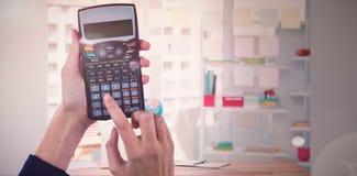 Составное изображение рук коммерсантки используя калькулятор Стоковые Изображения RF