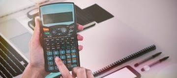 Составное изображение рук коммерсантки используя калькулятор Стоковое Фото