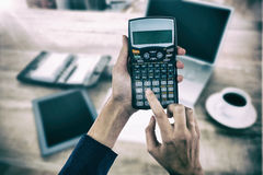 Составное изображение рук коммерсантки используя калькулятор Стоковое Изображение