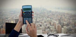 Составное изображение рук коммерсантки используя калькулятор Стоковые Фото