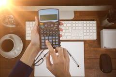Составное изображение рук коммерсантки используя калькулятор Стоковые Изображения
