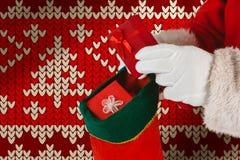 Составное изображение Санта Клауса кладя настоящие моменты в чулки рождества стоковое фото