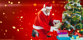 Составное изображение Санта Клауса аранжируя настоящие моменты приближает к рождественской елке Стоковое фото RF