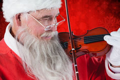 Составное изображение Санта Клауса играя скрипку Стоковые Фотографии RF