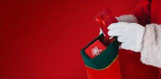 Составное изображение Санта Клауса кладя настоящие моменты в чулки рождества стоковая фотография