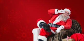 Составное изображение Санта Клауса сидя на софе с мешком подарка на рождество около его Стоковые Фотографии RF