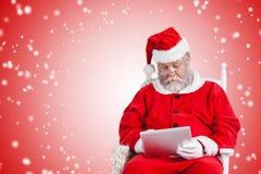Составное изображение Санта Клауса смотря кино на цифровой таблетке Стоковые Изображения