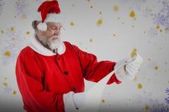 Составное изображение Санта Клауса усмехаясь и читая перечень Стоковое Изображение RF