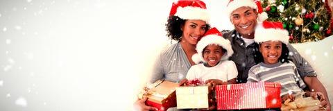 Составное изображение семьи держа подарки на рождество стоковая фотография rf