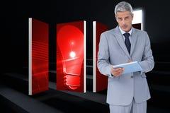 Составное изображение серьезного бизнесмена используя ПК таблетки смотря камеру Стоковая Фотография