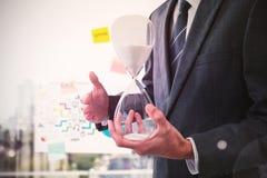 Составное изображение среднего раздела бизнесмена держа часы Стоковое Изображение RF