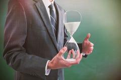 Составное изображение среднего раздела бизнесмена держа часы Стоковые Фото