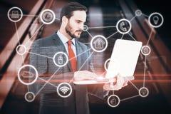Составное изображение сфокусированного бизнесмена используя его компьтер-книжку Стоковое фото RF