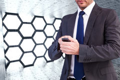 Составное изображение сфокусированного бизнесмена отправляя СМС на его мобильном телефоне Стоковые Изображения