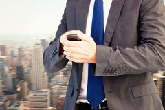 Составное изображение сфокусированного бизнесмена отправляя СМС на его мобильном телефоне Стоковые Фото