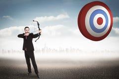 Составное изображение сфокусированного бизнесмена снимая лук и стрелы Стоковая Фотография